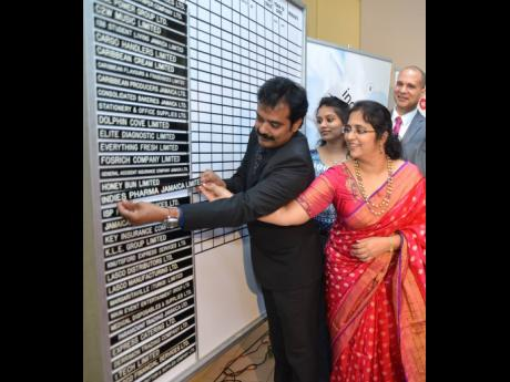 In this August 2018 Gleaner file photo, husband and wife business partners Guna Muppuri and Vishu Muppri insert the Indies Pharma strip on the listing board at the Jamaica Stock Exchange. .
