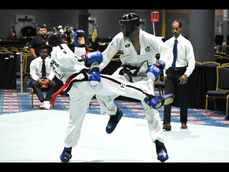 Nicholas Dusard (left) and fellow Jamaica combined martial arts teammate, Adrian Moore, clash in a feisty middleweight (-70kg) semi-final match of the International Taekwondo Associations  (International Taekwondo Federation) US Open Challenge Championships at the Coronado Springs Resort in Orlando, Florida, yesterday. Dusard won the bout and the division.