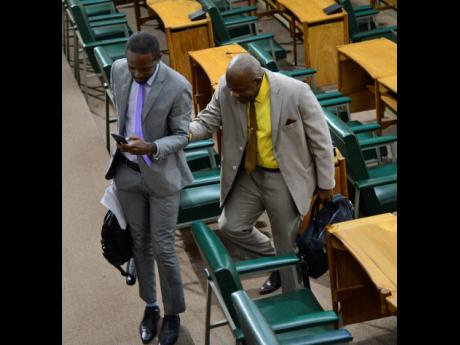 Senator Dr André Haughton (left) assists his colleague Dr Floyd Morris, who is visually impaired, to leave the House floor as opposition members walked out of the Senate yesterday.