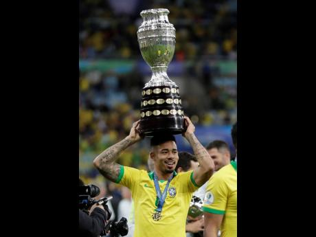 Brazil's Gabriel Jesus holds the Copa America trophy on his head as he celebrates his side's 3 -1 victory over Peru during the final at the Maracanã Stadium in Rio de Janeiro, Brazil, yesterday.