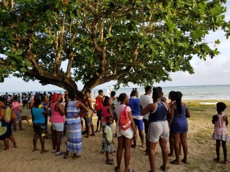Residents gather at the Lyssons Beach yesterday, where the body of 12-year-old Oshane Crawford was found after he disappeared while bathing at the nearby Diamond beach on Saturday.