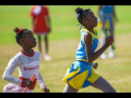 Theana Delahaye (right) of Spring Village anchors her team to victory ahead of Tatiana Williams in the girls' 4x100m relay at the CVSS Games 2019 held at the UWI Mona Bowl on Saturday, July 6.