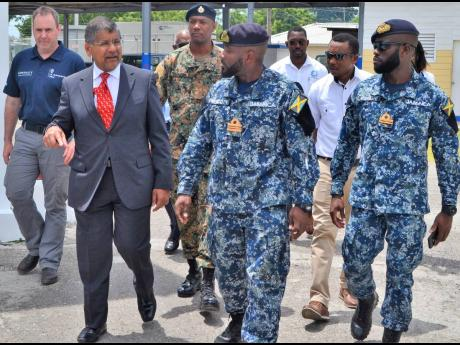 British High Commissioner Asif Ahmad (left) engages LCdr Aceion Prescott (centre), commanding officer of the Jamaica Defence Force Coast Guard, and other officers as he arrives at the Coast Guard base in Port Royal, Kingston.