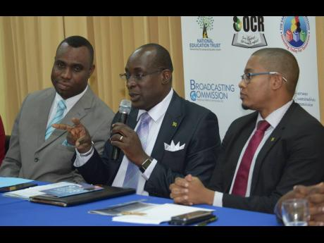 Then Minister of Education Senator Ruel Reid addresses a press conference in this February 2017 Gleaner file photo. At left is then Permanent Secretary Dean-Roy Bernard and at right is then State Minister Floyd Green.