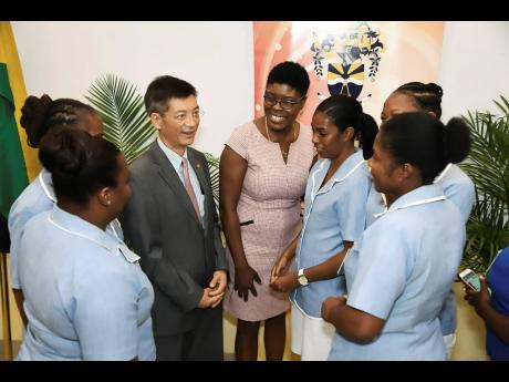 Fan Jianghong (third left), commercial and economic counsellor, Chinese Embassy in Jamaica, and Dr Adella Campbell (centre), head, Caribbean School of Nursing, interact with critical-care nursing students from the University of Technology.