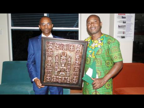 He likes it, so he buys it. Jamaica Defence Force Chief of Staff Lieutenant Rocky R. Meade (left) is now the owner of 'Onile' ('The Owner of the Nile'). Here, he poses with it and the artist himself, Alao Luqman.