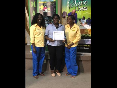 Coach Marlene Hawthorne (centre) receives her certificate from Delores McGregor (left) and   Sharon Thompson, both nurses.