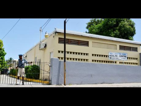 An elderly man exits  the  Rollington Town Health Centre , in St  Andrew.