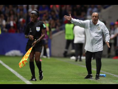 Jamaican assistant referee Princess Brown (left) moves about her touchline as Brazil head coach Vadao gives directions to his players during the FIFA Women's World Cup round-of-16 match between France and Brazil at the Oceane Stadium in Le Havre, France, on Sunday, June 23.