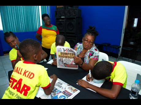 Humble Lion FC team manager Ingrid Smith interacts with The STAR Ball Kids during a day of activities held by the Gleaner Company (Media) Limited at its headquarters at 7 North Street, Kingston, yesterday.