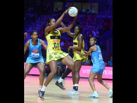 Jamaica's Romelda Aiken (second left) collects the ball ahead of Kelera Nawai (left) and Episake Kahatoka (right) of Fiji as Aiken's teammate, Jhaniele Fowler, covers during their Vitality Netball World Cup game at the M&S Bank Arena in Liverpool, England, yesterday.