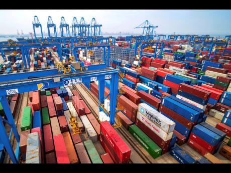In this Tuesday, May 14, 2019 photo, containers are piled up at a port in Qingdao in east China's Shandong province.