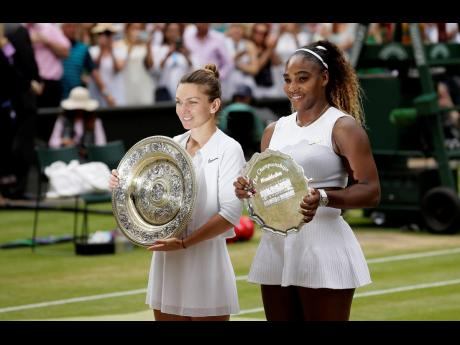 Winner Simona Halep (left) and second-place Serena Williams pose with their trophies after the women's singles final match of the Wimbledon Tennis Championships in London, yesterday. Halep won 6-2, 6-2.