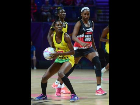 Jamaica's Shanice Beckford (left) gets the attention of Trinidad and Tobago's Rhonda John-Davis during their Netball World Cup match at the M&S Bank Arena in Liverpool, England, yesterday. The Jamaicans won 68-43 and will face South Africa today at 11:00 a.m.