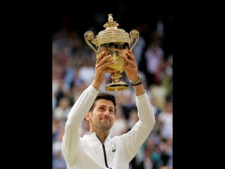 Serbia's Novak Djokovic lifts the trophy after defeating Switzerland's Roger Federer in the men's singles final match of the Wimbledon Tennis Championships in London, England, yesterday.