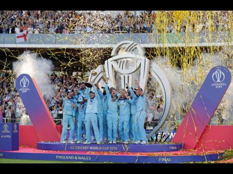 England's captain Eoin Morgan raises the trophy after winning the ICC World Cup final match against New Zealand at Lord's cricket ground in London, yesterday.