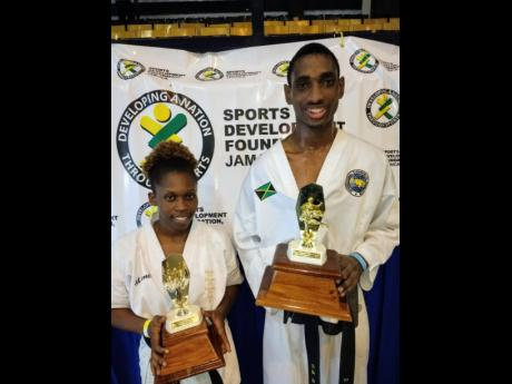 Marissa Jones of Rising Sun Karate and Delano Francis of Jamaica Taekwondo show off their grand champion trophies won at the recent Seido Karate Open Championships at the University of Technology, Jamaica, auditorium.