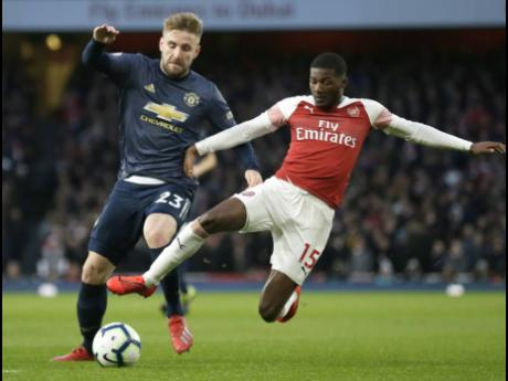 Arsenal's Ainsley Maitland-Niles (right) challenges Manchester United's Luke Shaw for the ball during an English Premier League match at the Emirates Stadium in London, England, on Sunday, March 10.