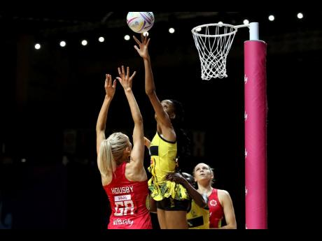 England's Helen Housby (left) and Jamaica's Shamera Sterling (top) battle for the ball during their Vitality Netball World Cup match in Liverpool, England this morning. (Nigel French/PA via AP)