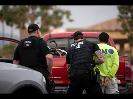 In this July 8, 2019 photo, US Immigration and Customs Enforcement officers detain a man during an operation in California. The carefully orchestrated arrest last week in this San Diego suburb illustrates how President Donald Trump's pledge to start deporting millions of people in the country illegally is virtually impossible with ICE's budget and its method of picking people up, according to critics.