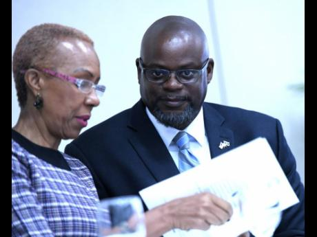 Energy Minister Fayval Williams speaks with Jason Fraser, USAID country representative, at the opening ceremony for the Jamaica Alternative Energy Conference at Spanish Court Hotel in New Kingston yesterday.
