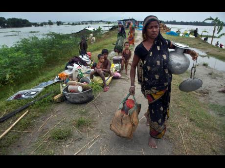 An Indian woman carries her belongings on an embankment to take shelter in Pabhokathi village, east of Gauhati, India.