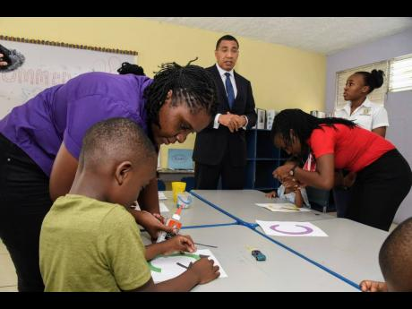 Prime Minister Andrew Holness (centre) observes as teachers from the Special Needs Department at Liberty Academy at the Priory in St Andrew, Jami-Ann Genius (left) and Tamalee Hamilton (right), interact with students during a visit to the institution yesterday.