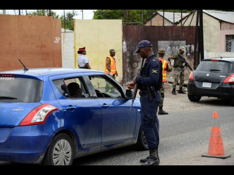 Members of the Jamaica Defence Force and the Jamaica Constabulary Force (JCF) conducting operations at a checkpoint along Waltham Park Road in the St Andrew South Police Division last Wednesday. The security measure, which was last week declared for an initial period of 14 days, has been extended until September.