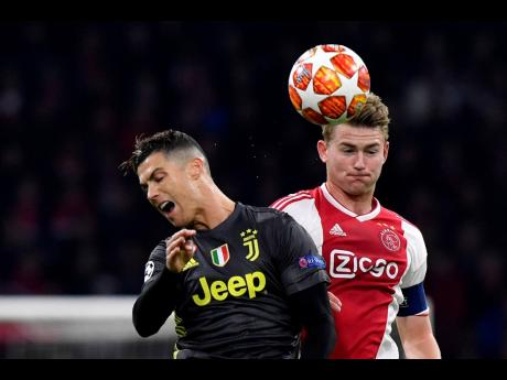 In this Wednesday, April 10, 2019 file photo, Ajax's Matthijs de Ligt (right) fights for the ball with Juventus' Cristiano Ronaldo during the Champions League quarter-final first-leg match between the two teams at the Johan Cruyff Arena in Amsterdam, the Netherlands. Defender Matthijs De Ligt has signed with Juventus.