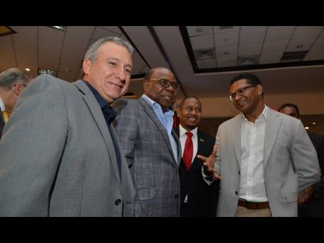 Tourism Minister Edmund Bartlett (second left) shares a moment with Floyd Green (second right), minister of state in the Ministry of Industry, Commerce and Agriculture; Richard Pandohie (right), newly elected president of the JMEA; and Metry Seaga, immediate past JMEA president and chairman of the Manufacturing Technical Working Group, at the launch of the fifth staging of the Christmas in July at The Jamaica Pegasus hotel yesterday.