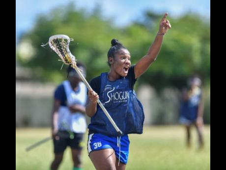 Shanice Thompson shouts instructions to a teammate as she runs towards the D in a training session for the national under-19 women's lacrosse team at Wolmer's High School for Girls earlier this year.