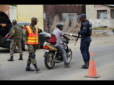 Members of the Jamaica Defence Force and the Jamaica Constabulary Force manning a security checkpoint along a section of Waltham Park Road under the state of emergency in the St Andrew South Police Division on July 10.