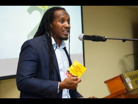 Junior Youth Minister Alando Terrelonge holds a copy of the Children Protection Laws pocket booklet while speaking at a child protection seminar and booklet launch at the UWI Regional Headquarters on Thursday.