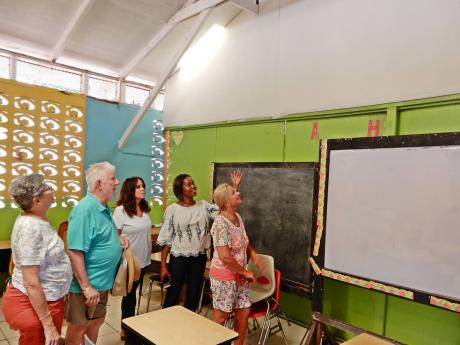 Principal Slean Harris (second right) shows the area where repairs were done to a classroom at Three Hills Primary School in Charles Town, St Mary. Others in the photo are (from left) Jane Saks, Gene Saks, Alex Ghisays and Darcy Fangman.