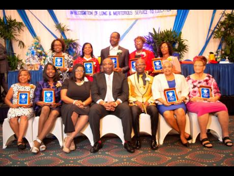 Front row (from left): Paulette Battick-Smith; Christine DeSilva-Campbell; Georgia Waugh Richards; Dr Garth Anderson, president, Jamaica Teachers' Association (JTA), Owen Speid, president-elect, JTA; Sharon Reid; and Jean Romans. Back row (from left): Ann Marie Hayles, Paulette Kennedy, Everton Walters, Judith Hutchinson and Clova Wright. The educators were specially awarded for having given 41 years of service to education in their respective schools islandwide.  Contributed
