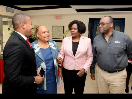 Minister of State in the Ministry of Industry, Commerce, Agriculture, and Fisheries, Floyd Green (left), is in discussion with (from second left): Executive Director of Jamaica Business Development Corporation, Valerie Veira; Permanent Secretary in the Ministry of Tourism, Jennifer Griffith; and Director of Tourism, Donovan White, during the fifth staging of the Christmas in July trade show at The Jamaica Pegasus hotel in New Kingston on July 18.