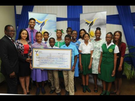 Wayne Mckenzie (left), president and CEO of West Kingston Power Partners & Jamaica Energy Partners (JEP), and Melissa Newman (second left), public and community relations specialist, handing over the cheque to recipients  from west Kingston. The scholarships, which were awarded to more than 30 secondary and tertiary-level students, were presented at the JEP head office on Marcus Garvey Drive in Kingston.