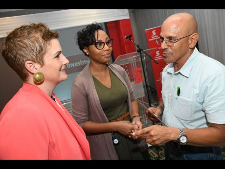 Debra Lopez Spence (left), vice-president, sales and service of Scotia Investments and Wealth, and Tameka Walker-Mowatt, senior financial analyst of Scotia Investments, chat with Eddie Cousins of Lydford Mining company at the Scotia Investments Client Connect and Invest breakfast series at the Marriott Courtyard in New Kingston last Thursday.