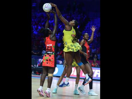 Jamaica's Stacian Facey (centre) makes a big block on Malawi goal attack Jane Chimaliro (left) while Malawi goal shooter Sindi Simtowe (right) prepares herself for a possible rebound during their fifth-place match in the Vitality Netball World Cup at the M&S Bank Arena in Liverpool, England, yesterday.