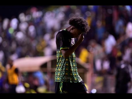 Jamaica Under-23 footballer Ricardo Thomas hangs his head in shame after the team's failure to advance to the next round of Olympic football qualifying.