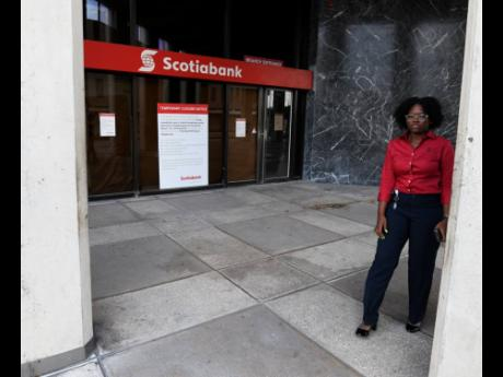 A temporary closure notice at the entrance to the Scotiabank Centre and Executive Branches at the intersection of Duke and Port Royal streets in downtown Kingston.