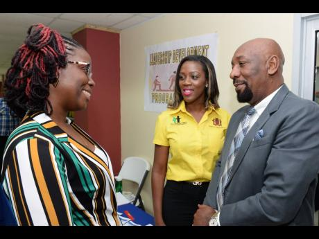 Minister of State in the Ministry of National Security Rudyard Spencer (right) in conversation with Programmes Manager, HEART Trust/NTA, Diandra Barrett (left), at the We Transform Youth Empowerment Programme mentorship training session on  Friday (July 19), at the ministry, on Oxford Road, St Andrew. At centre is  We Transform Programme Director Ella Gharty.