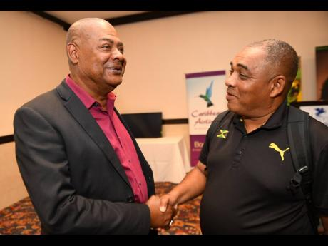From left: Jamaica Football Federation President Michael Ricketts greets Reggae Girlz head coach Hue Menzies ahead of a press conference held at the Jamaica Pegasus yesterday, where the members of the country's women's football team for the Pan Am Games were introduced.