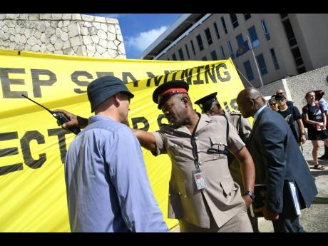 Inspector Phillip Smith (second left) speaks to Frank Hewetson (left), Greenpeace International coordinator, as they police yesterday tried to get the environmental activists to relocate from the entrance of the Jamaica Conference Centre in downtown Kingston, where the International Seabed Authority (ISA) annual meeting was under way. The Jamaica Environment Trust and representatives of other civil society groups also joined the protest against deep-sea mining.
