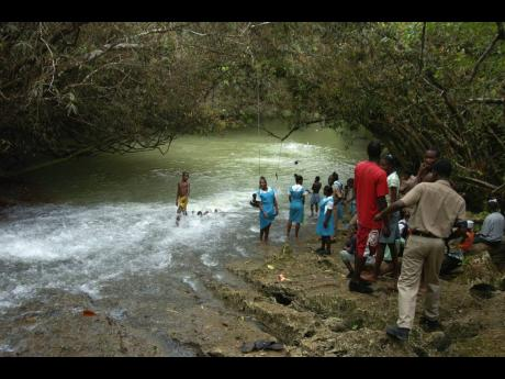 Students enjoy the river at The Falls at Two Hills after the launch of the Cockpit Country local forest management committees in Bunkers Hill, Trelawny, on March 28, 2007.
