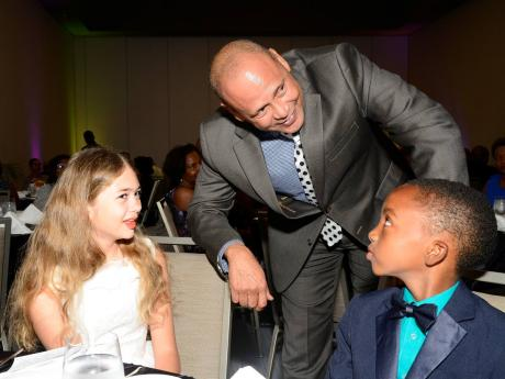 Guardian Life Limited President Eric Hosin speaks with Rachel Gammon, the top-performing girl in the inaugural PEP exams, and Dominic Haisley, the top boy, at the annual Guardian Group Scholarship Awards luncheon at the AC Marriott Hotel in St Andrew yesterday.