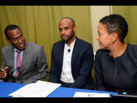 Finance Minister Dr Nigel Clarke (left) makes a point to Gladys Young (right), senior legal officer, CARICOM Secretariat, and Andrei Bennett, chief public procurement policy officer in the Ministry of Finance and the Public Service. The occasion was the Jamaica Chamber of Commerce's 2019 procurement seminar at the Knutsford Court Hotel in New Kingston on Tuesday.