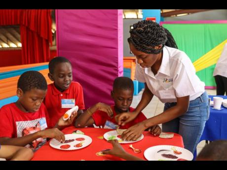 Shanice Paul assists children to build a balanced meal, choosing foods from each of the food groups in arts and craft session during The Nestlé Jamaica Health and Wellness Foundation's inaugural Nestlé for Healthier Kids Unstoppable Kids Camp, inspiring kids to lead healthier lives through a series of engaging educational games and activities.