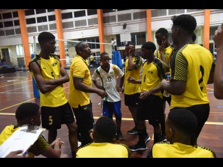Steve Davis (second left), coach of the Jamaica Under-19 male team, talks to his team between sets during their match against Suriname on Monday in the CASOVA Youth Volleyball Tournament at the G.C. Foster College of Physical Education and Sports.