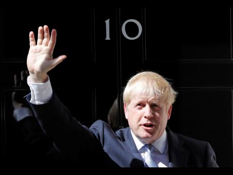 Britain's new Prime Minister Boris Johnson waves from the steps outside 10 Downing Street, London, yesterday. Johnson replaces Theresa May, following her resignation last month after Parliament repeatedly rejected the Brexit withdrawal agreement she struck with the European Union.